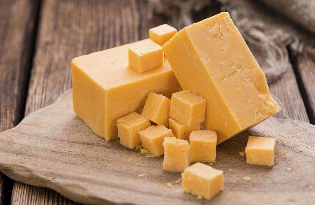 Cheddar cubes on a wooden plate