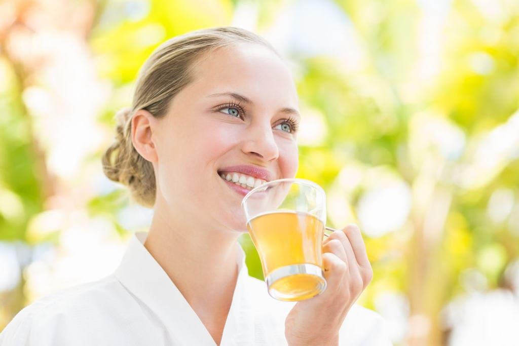 Young woman drinking a glass of kombucha