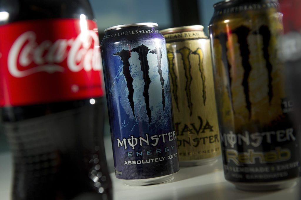 Cans of Monster Beverage energy drinks and a bottle of Coca-Cola