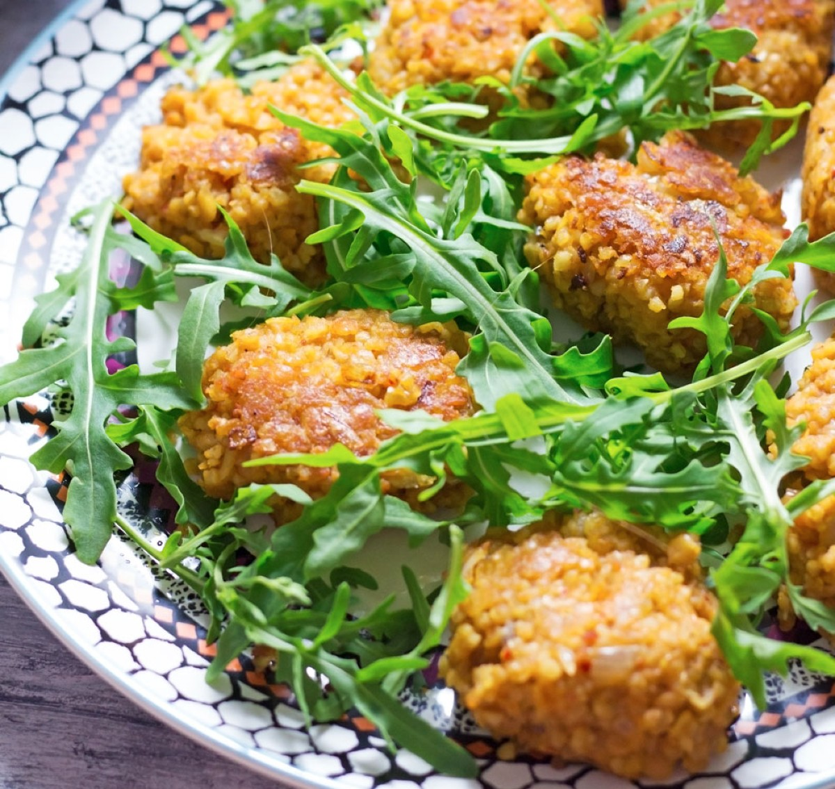 Lentil and bulgur wheat cakes served on a plate with arugula
