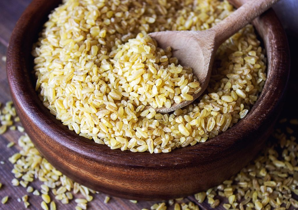 A wooden bowl and spoon full of fine bulgur wheat