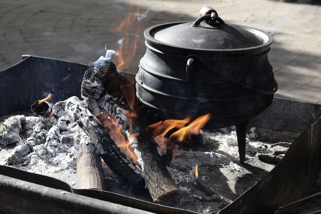 A pot of Potjiekos cooking in an open fire