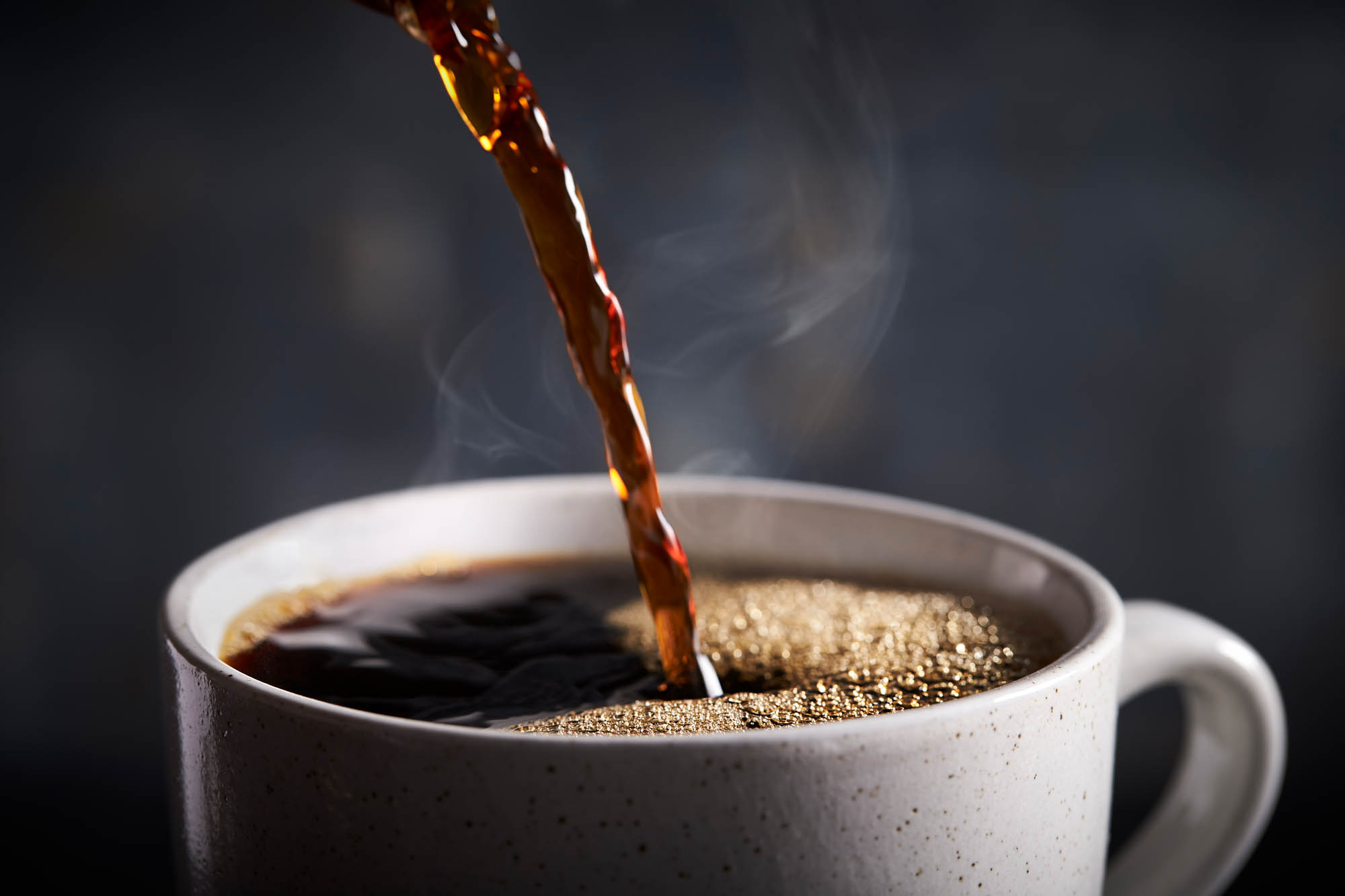 Pouring hot coffee in a mug